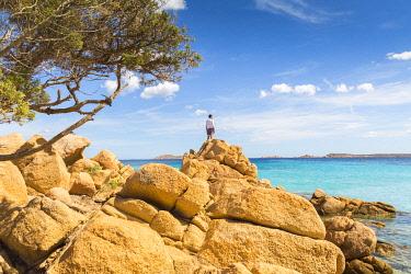 CLKAB68779 A young man admiring the view standing on rocks in Capriccioli beach, Arzachena Costa Smeralda, Olbia-Tempio province, Sardinia district, Italy