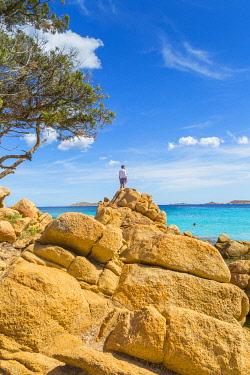 CLKAB68780 A young man admiring the view standing on rocks in Capriccioli beach, Arzachena Costa Smeralda, Olbia-Tempio province, Sardinia district, Italy