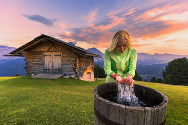 CLKFB95624 Girl washes herself in a tube at sunset. Gardena Valley, South Tyrol, Dolomites, Italy, Europe. (MR)