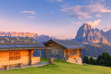 CLKFB95626 Traditional huts at sunset with Sassolungo and Sella Group in the background. Gardena Valley, South Tyrol, Dolomites, Italy, Europe.
