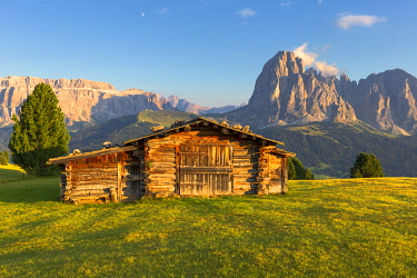 CLKFB95629 Last rays of sun on traditional hut with view on Sassolungo and Sella Group. Gardena Valley, South Tyrol, Dolomites, Italy, Europe.