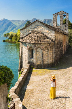 CLKGA94815 Young woman admiring San Giacomo church in Spurano, Ossuccio, Como province, Lombardy, italy (MR)