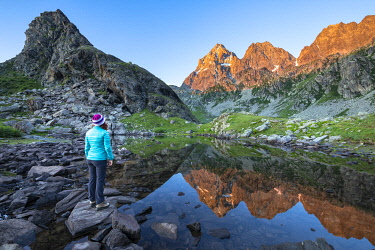 CLKGP95372 A girl is watching the Monviso Peak, reflected in a small alpine lake at sunrise. Fiorenza Lake, Pian del Re, Monviso Natural Park, Po Valley, Crissolo, Cuneo province, Piedmont, Italy, Europe (MR)