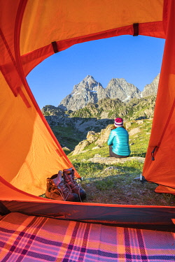 CLKGP95384 A girl is watching the Monviso Peak outside her tent. Fiorenza Lake, Pian del Re, Monviso Natural Park, Po Valley, Crissolo, Cuneo province, Piedmont, Italy, Europe  (MR)