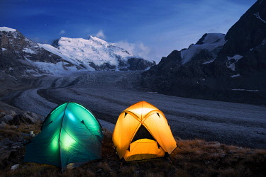 CLKMG94967 Illuminated tents by nigh camping close to the Grand Combin glacier, Grand Combin on background,Switzerland