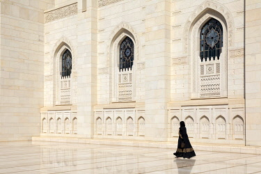 OMA2845AW An Omani woman  walks past the marble facade of Sultan Qaboos Grand Mosque, Muscat, Oman