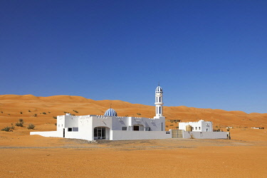 OMA2853AW A colourful mosque stands in front of sand dunes at the edge of the desert, Wahiba sands, Oman