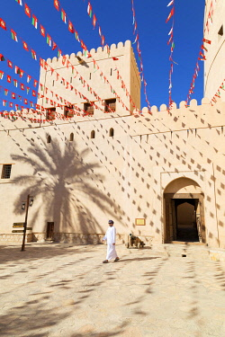 OMA2859AW An Omani man walks past Bahla Fort decorated to celebrate the birthday of Sultan Qaboos, Tanuf, Oman