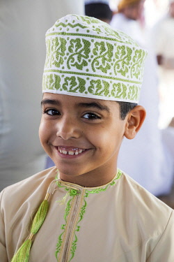 OMA2862AW A boy wearing a dishdasha and Kuma at the livestock market in Nizwa, Oman