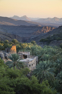 OMA2871AW Oman, Ad Dakhiliyah region, Al Hamra, Misfat Al Abreen, An old  house made of stone and earth surrounded by palm trees in the mountainous village of Misfat Al Abreen