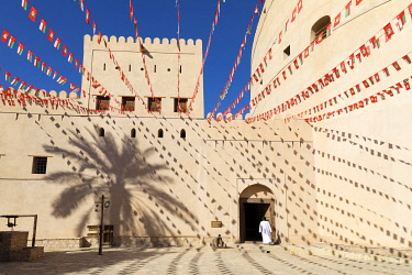OMA2876AW An Omani man walks into Bahla Fort decorated to celebrate the birthday of Sultan Qaboos, Tanuf, Oman