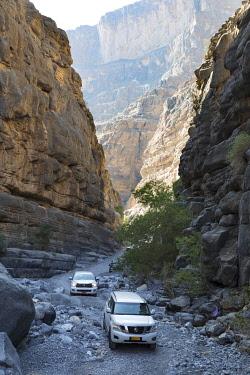 OMA2890AW Oman, Wadi Nakhr, 4 wheel drive vehicles drive through the deep canyon of Wadi Nakhr