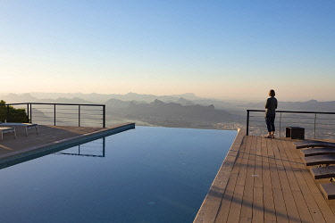 OMA2893AW A tourist looks out at the view from the swimming pool at The View hotel, Al Hamra, Oman