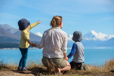 NZ9302 South Island, New Zealand, the view across Lake Pukaki to Mount Cook, a mother and her two children look out across the lake on a family holiday