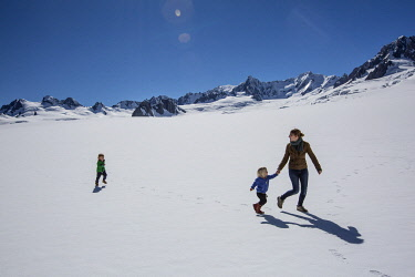 NZ9324 Fox Glacier, South Island, New Zealand, a mother and children run around in the snow at the top of the glacier