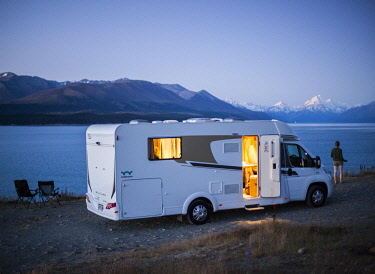 NZ9332 South Island, New Zealand, the view across Lake Pukaki to Mount Cook, a motor home, two camping chairs and a woman in the foreground