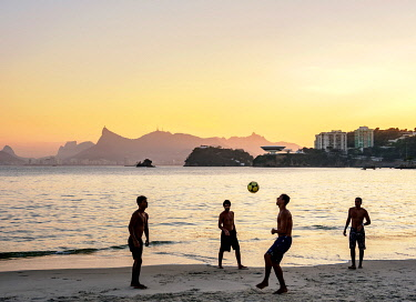 BRA3725AW People playing football on Icarai Beach at sunset, Niteroi, State of Rio de Janeiro, Brazil