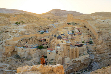ISR0708AW Palestine, West Bank, Bethlehem Governorate, Al-Ubeidiya. Hiker at Mar Saba monastery, built into the cliffs of the Kidron Valley in the Judean Desert. (MR)