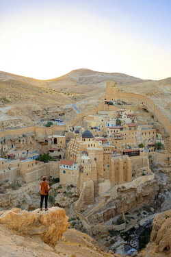 ISR0709AW Palestine, West Bank, Bethlehem Governorate, Al-Ubeidiya. Hiker at Mar Saba monastery, built into the cliffs of the Kidron Valley in the Judean Desert. (MR)