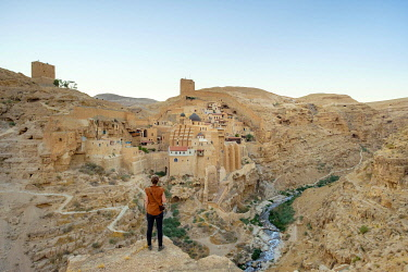 ISR0710AW Palestine, West Bank, Bethlehem Governorate, Al-Ubeidiya. Hiker at Mar Saba monastery, built into the cliffs of the Kidron Valley in the Judean Desert. (MR)