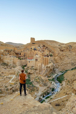 ISR0711AW Palestine, West Bank, Bethlehem Governorate, Al-Ubeidiya. Hiker at Mar Saba monastery, built into the cliffs of the Kidron Valley in the Judean Desert. (MR)