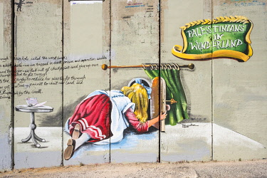 ISR0832AW Palestine, West Bank, Bethlehem Governorate, Bethlehem. Mural depicting Alice in Wonderland painted on the Palestanian side of the Israeli separation barrier.
