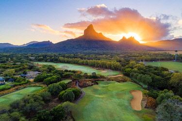 CLKAC103323 Aerial view of Tamarina golf course with Rempart mountain and Trois mamelles mountain during the sunrise. Tamarin, Black River (Riviere Noire), West coast, Mauritius, Africa