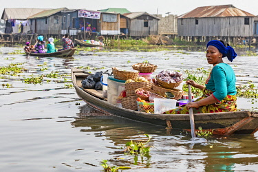 BNN0101 Benin, Ganvie, Lake Nokoue, Atlantique Department.  A woman paddles her floating mobile shop at Ganvie, a lake village on Lake Nokoue. Ganvie is believed to be the largest village of its kind in Afric...