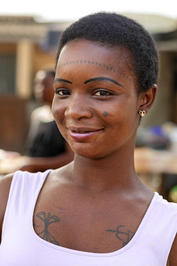 BNN0127 Benin, Grand Popo, Mono Department.  An attractive girl with traditional tattoos and make-up at a market stall near the border with Togo.