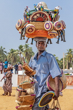 BNN0156 Benin, Ouidah, Atlantique Department.  A street seller in Ouidah balances a basket with a large selection of merchandise on his head. Ouidah is the spiritual centre of Benin.