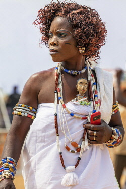 BNN0157 Benin, Ouidah, Atlantique Department.  A woman with a voodoo doll tucked into her dress attends the annual voodoo festival held in January each year.
