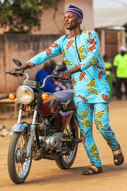 BNN0158 Benin, Ouidah, Atlantique Department.  A motor cyclist in bright traditional dress.