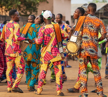 BNN0161 Benin, Ouidah, Atlantique Department.  Drummers and musicians in bright clothing sing while beating out the rhythm for Egungun masked dancers to perform at a lively voodoo celebration.