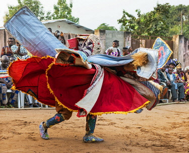 BNN0166 Benin, Ouidah, Atlantique Department.  An Egungun masked dancer in brilliant sequined costume dances at a lively voodoo celebration.  The dancers represent Yoruba ancestral spirits which give guidance...