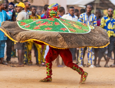 BNN0171 Benin, Ouidah, Atlantique Department.  An Egungun masked dancer spins his sequined round cape at a lively voodoo celebration.  The dancers represent Yoruba ancestral spirits which give guidance to the...