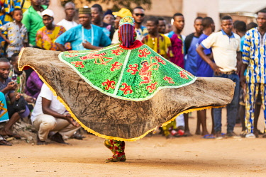BNN0172 Benin, Ouidah, Atlantique Department.  An Egungun masked dancer spins his sequined round cape at a lively voodoo celebration.  The dancers represent Yoruba ancestral spirits which give guidance to the...