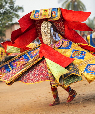 BNN0179 Benin, Ouidah, Atlantique Department.  An Egungun masked dancer in brilliant sequined costume dances at a lively voodoo celebration.  The dancers represent Yoruba ancestral spirits which give guidance...