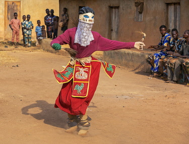 BNN0213 Benin, Ketou, Plateau Department.  A masked dancer representing the female sex.  The mask fits onto a dancer's head with his face covered by a veil.  The dances are educational promoting harmony among...