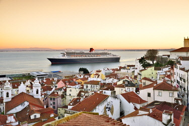 POR10220AW The iconic cruise ship Queen Mary II on the Tagus river facing the traditional moorish Alfama district. Lisbon, Portugal
