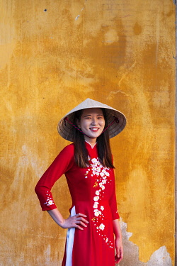 VIT1510AW South East Asia, Vietnam, Quang Nam, Hoi An, An attractive young woman in a traditional red Ao Dai dress in the old Unesco World Heritage town of Hoi An MR