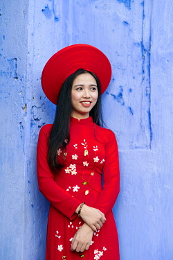 VIT1514AW South East Asia, Vietnam, Quang Nam, Hoi An, An attractive young woman in a traditional red Ao Dai dress in the old Unesco World Heritage town of Hoi An MR