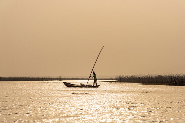 BNN0321AW Africa, Benin, Lake Nokoué. A fisherman in his typical wooden canoe near to  the famous stilt village of Ganvie.