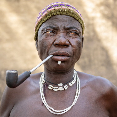 TOG0030AW Africa, Togo. Koutammakou, Tamberma people. Unesco World Heritage site. Portrait of an elder woman with a wild boar tooth in her lower lip