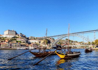 POR10335AWRF Traditional boats on Vila Nova de Gaia bank of Douro River, Dom Luis I Bridge in the background, Porto, Portugal