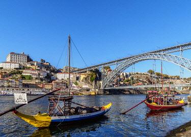 POR10369AW Traditional boats on Vila Nova de Gaia bank of Douro River, Dom Luis I Bridge in the background, Porto, Portugal