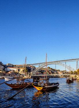 POR10370AW Traditional boats on Vila Nova de Gaia bank of Douro River, Dom Luis I Bridge in the background, Porto, Portugal