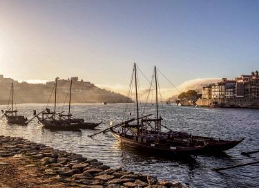 POR10372AW Traditional boats on Vila Nova de Gaia bank of Douro River, Porto Skyline in the background, Portugal