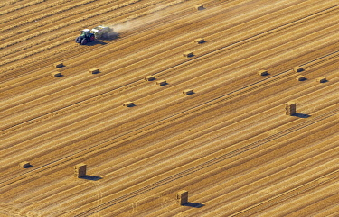 IBLBLO03769266 Aerial view, straw bales and tractor in a cornfield, North Rhine-Westphalia, Germany, Europe