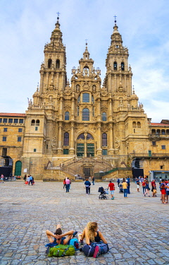 SPA8906AW Spain, Galicia, Santiago de Compostela, cathedral. Couple resting on backpacks. UNESCO World Heritage site