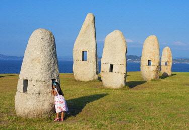 SPA8827AW Spain, Galicia, La Coruna, menhirs, girl looking through menhir (MR)